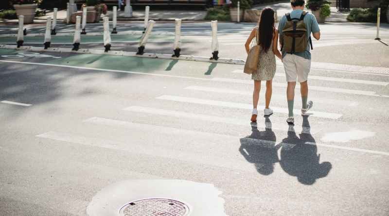 unrecognizable couple crossing road in sunny city