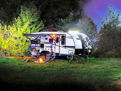 Couple sitting in front of campfire withTravel Trailer in background