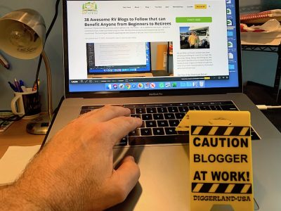 hand over laptop keyboard with a mini construction sign that says CAUTION BLOGGER AT WORK!