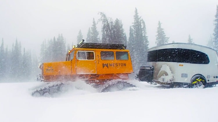 airstream in winter towed by a snow cat