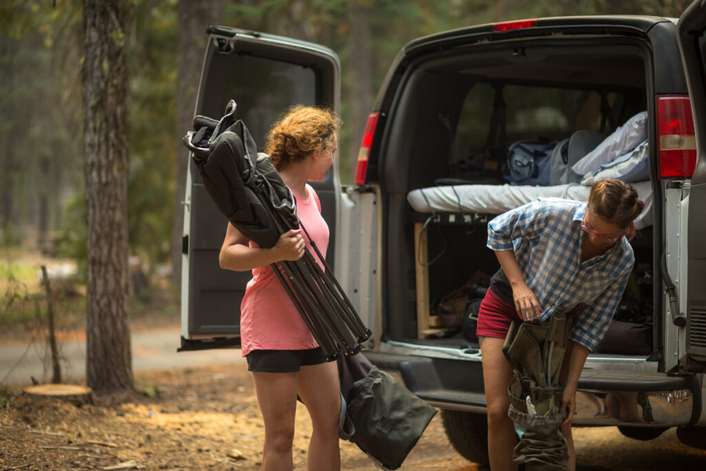 2 women unloading camping chairs from a campervan