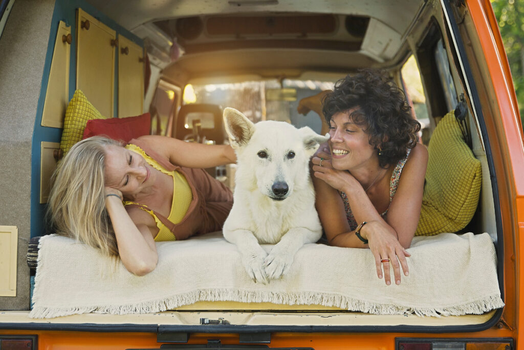Two woman and a white dog laying in the back of a van