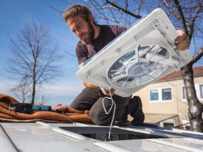 man installing a rooftop fan into a van