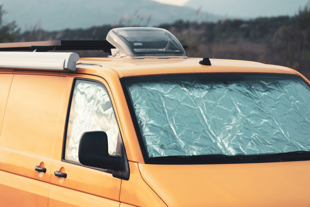 Yellow campervan with insulated window covers in windshield and passenger window