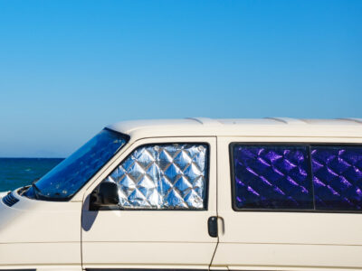 campvan with interior window covers parked by the ocean