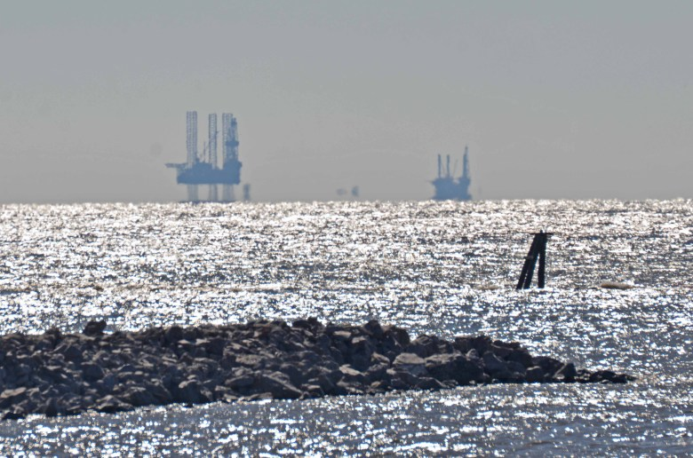 Offshore platforms that support the submerged oil and gas wells in the Gulf of Mexico visible from the Louisiana coastline.