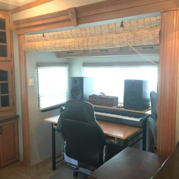 Office and music area in fifth wheel RV with reed roll-up shade