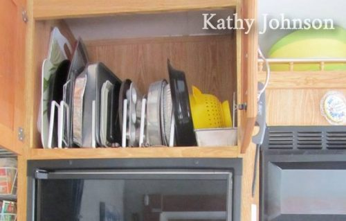 Baking pans and dishes stored vertically inside #RV #kitchen cabinet