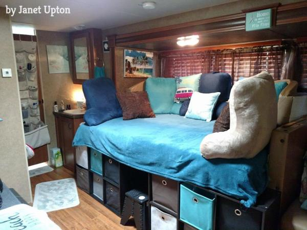 RV dinette booth converted to sofa bed with full sized memory foam mattress and cube storage shelves | by Janet Upton