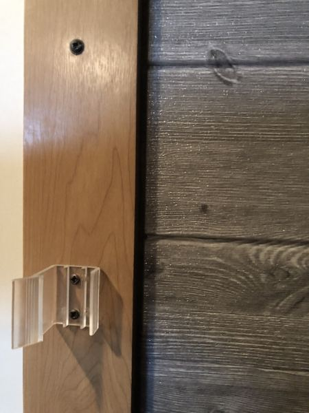 Faux shiplap wood plank wall made of adhesive foam panels in RV closet