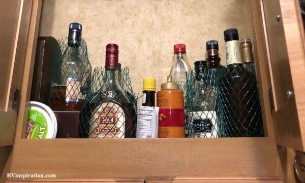 Mesh liquor sleeves for protecting glass bottles in RV kitchen