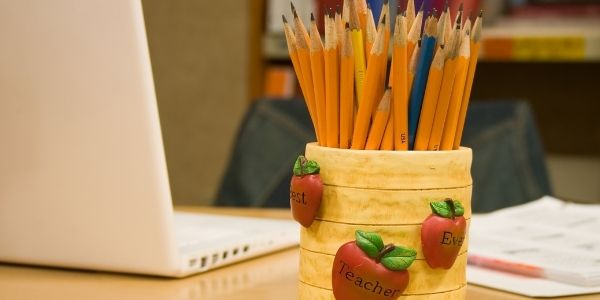 Pencils in a cup on a teacher's desk