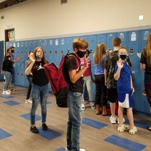 Students wave to camera in hallway