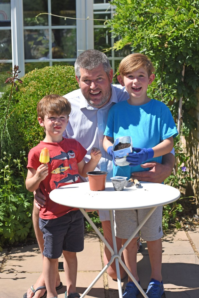 Phil Carter, head Gardener at Windsor Castle with sons Noah (6) and Jack (3). using a yogurt carton and milk bottle to plant their seeds. Picture by Emma Sheppard