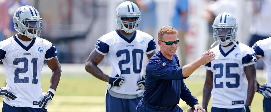 Dallas Cowboys head coach Jason Garrett (center) demonstrates to running backs Joseph Randle (21), Darren McFadden (20) and Lance Dunbar (25) during an NFL football organized team activity, Wednesday, June 3, 2015, in Irving, Texas. (AP Photo/James D Smith)