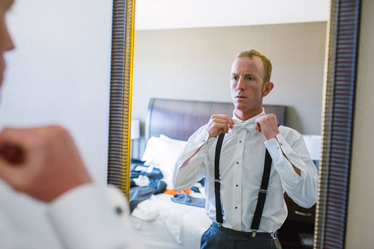 groom getting ready with bowtie in mirror