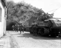 Soldiers of the 55th Armored Infantry Battalion and tank of the 22nd Tank Battalion, move through smoke filled street. Wernberg, Germany. April 22, 1945.