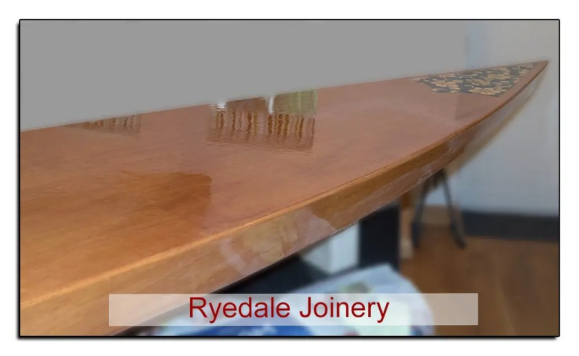 Image of varnished wooden paddle board.