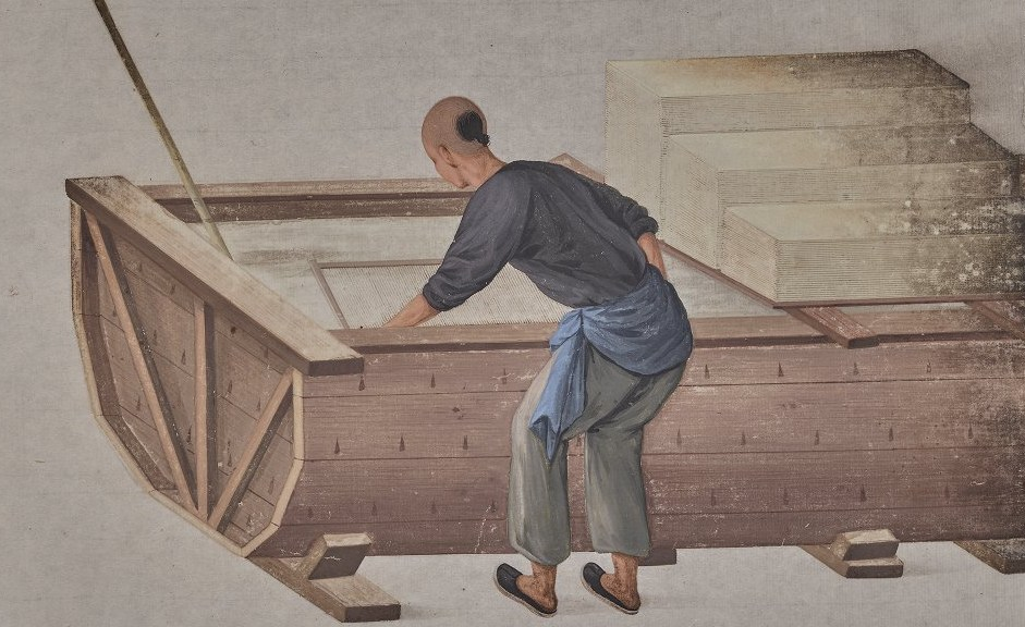 An illustration of a person dipping a mesh screen into a vat of paper pulp