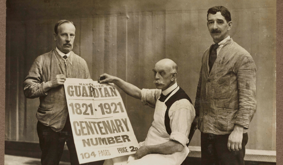 Black and White photograph of three men holding the centenary edition of the Guardian