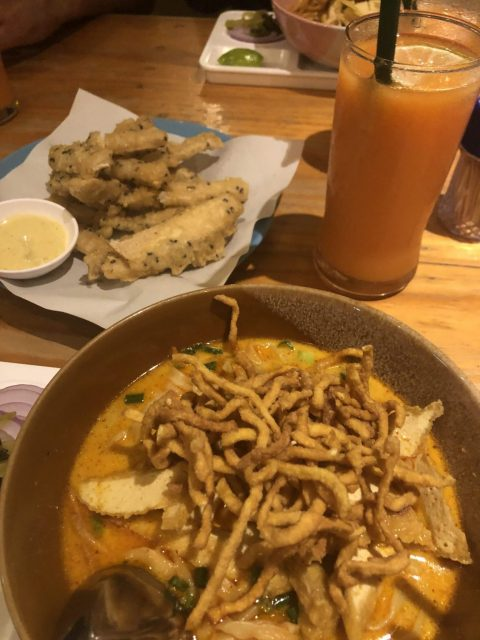 Picture of tofu Khao Soi, passionfruit smoothie, and some veg pakora in Pai