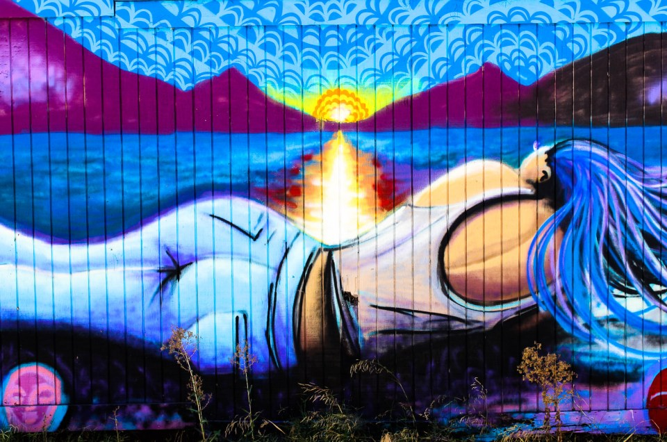 mural of woman laying down watching sunset
