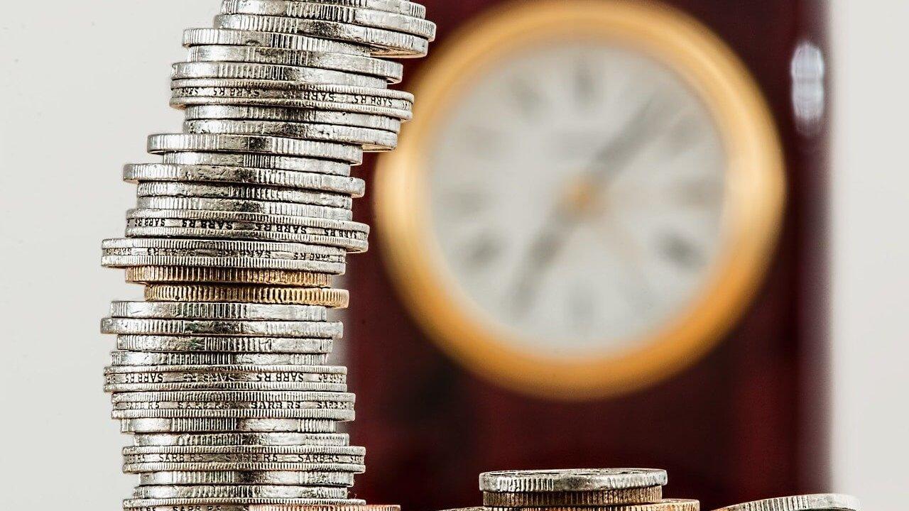時計をバックに小銭が積み上がっている画像