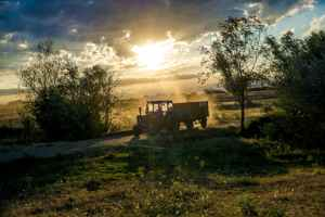 tractor with trailer under cloudy skies during day