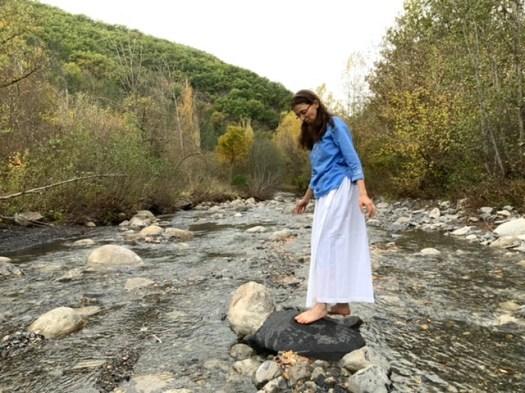 Jeune femme marchant sur les pierres d'une rivière