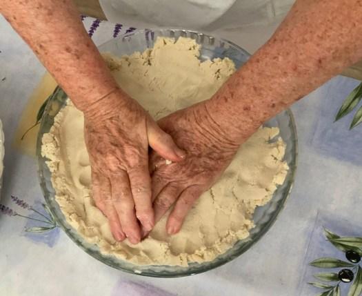 Des mains qui étalent une pâte à tarte