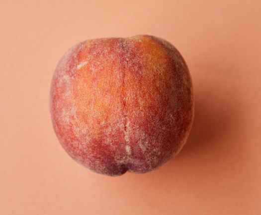 fresh juicy pink peach on pink surface