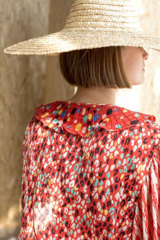 calm woman in colorful dress and straw hat