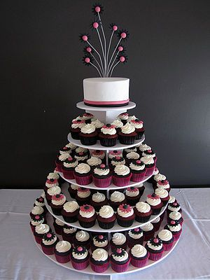 This cupcake cake shows a mini cake at the top which the bride and groom can cut