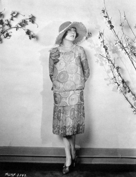 1920s Fashion Black and White Photograph Woman with Floral Dress Heels and Hat Dropped Waist Dress