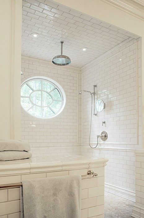 White subway tile walk in shower, no glass, circular window, tiled ceiling, rain showerhead, handheld showerhead....: