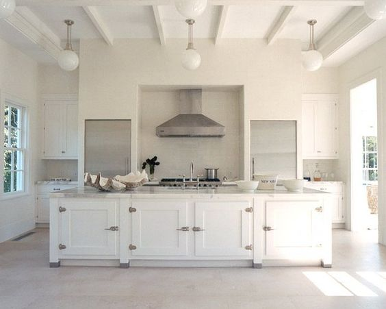 Simple, White, Modern, Symmetrical kitchen. Custom cabinets by St. Charles of New York fitted with reclaimed nickel icebox latches to match Viking's stainless steel chimney wall hood, cafeteria lights are from Urban Archaeology,Design by Haynes-Roberts for their own home.: