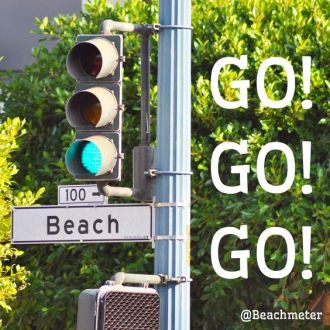 Green traffic light and beach street sign