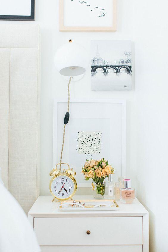 Inspiração para criado mudo estiloso: despertador clássico no dourado, flores, perfume e bandeja para jóias e acessórios.: