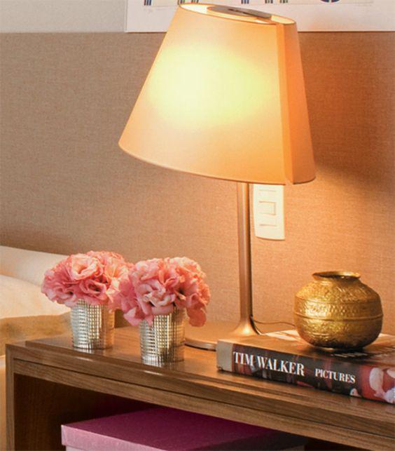Vasinhos prateados com flores cor-de-rosa (Esther Giobbi) e caixa de seda no mesmo tom (Empório Beraldin). Com estrutura de alumínio e cúpula de policarbonato, o par de abajures (La Lampe) não deixa a luz ir direto aos olhos.: