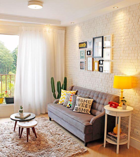 Quadrinhos, almofadas, um cactus e um abajur amarelo vibrante colorem esta sala de estar de mobiliário de tons sóbrios.: