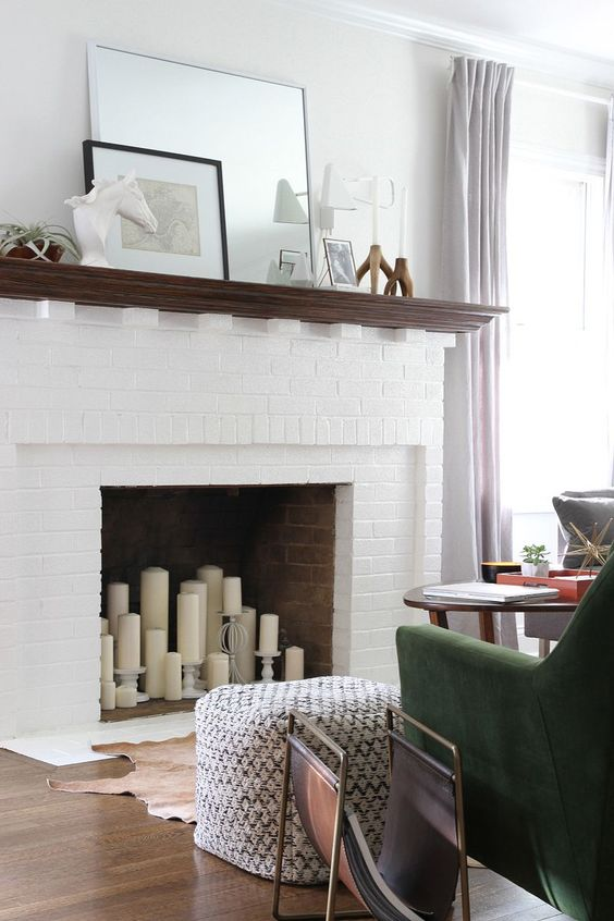 Fill an unusable fireplace with different sized candles and holders in the same color.: