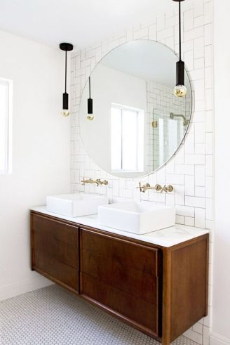 Unusual subway tile arrangement in bathroom with round mirror and pendant lights.: