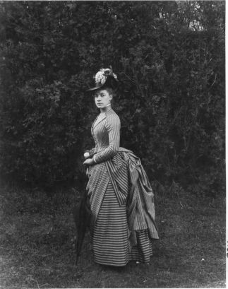"""""""Twenty-two-year-old Miss E. Alice Austen poses in her Sunday best - a smart overskirt and a hat decorated with white lilacs. She holds a parasol and a silver change purse. Photo taken in June 1888 by Captain Oswald Muller."""" #Victorian #fashion #women #photography:"""