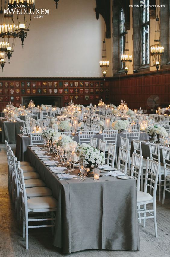 Family style reception with white chiavari chairs, gray table linens, candlelight, white flowersWedLuxe Magazine:
