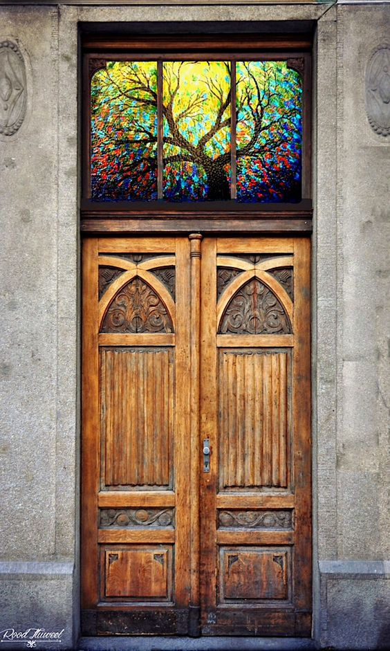 Stained glass over a carved wooden door (location unknown):