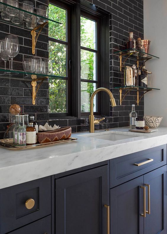 designed by architect Wilson Fuqua, with interiors by Theresa Rowe. love the contrast in this kitchen. white grout keeps the black tile from overpowering and the gold accents really make the space pop.: