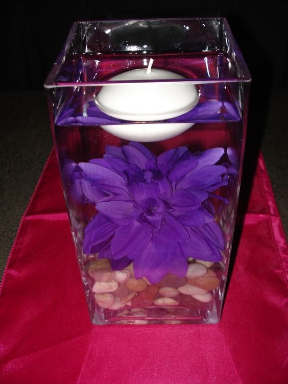 Purple Flower On River Rocks In Water With Floating Candle
