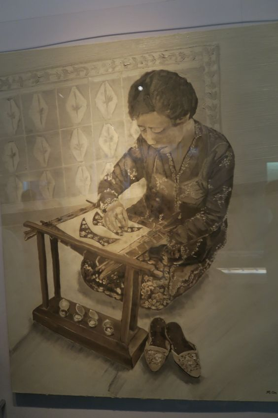 A Peranakan beading-frame. The lady in the picture is beading the highly decorative uppers for a pair of traditional slippers.