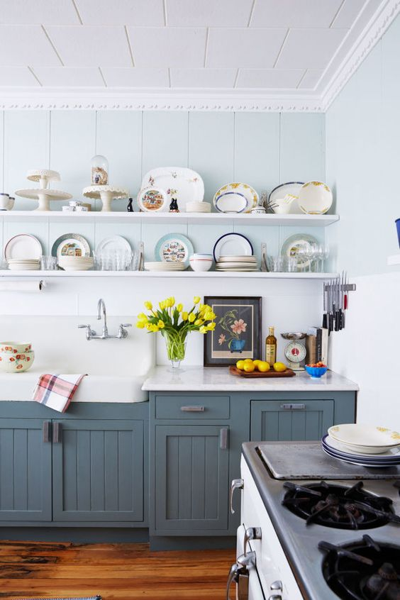 This dark, run-down kitchen was transformed into an inviting space full of country charm. The lower cabinets are painted dark gray-blue and open shelving shows off a collection of souvenir plates alongside cake stands, enamelware, and sweet little pie birds.: