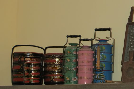 Antique Peranakan tiffin-carriers (three on the right) are immediately distinguishable because of their bright colours, and floral decorations.
